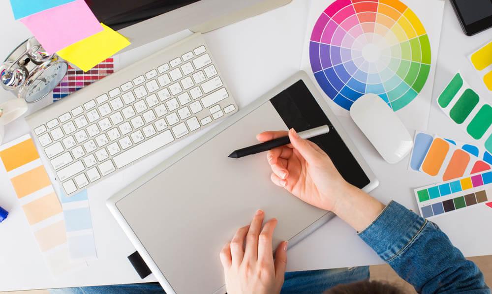An image of a digital designer drawing on a digital pad.