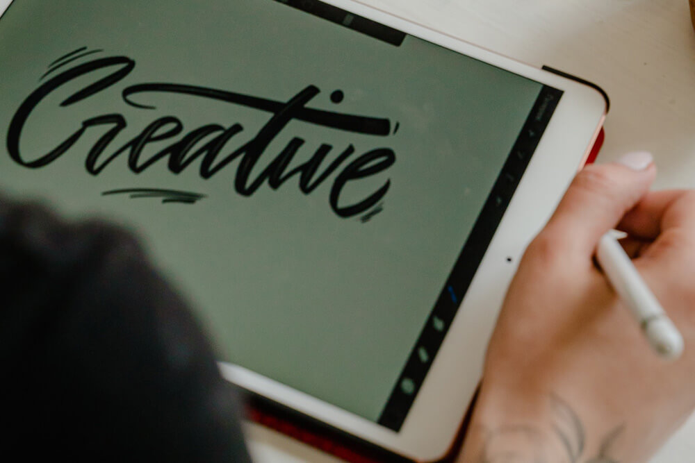 An image of a digital artist creating on an art pad for graphic design solutions.